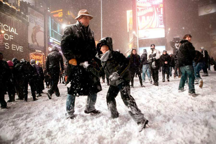 A snowball fight in Times Square, with faces blurred out.